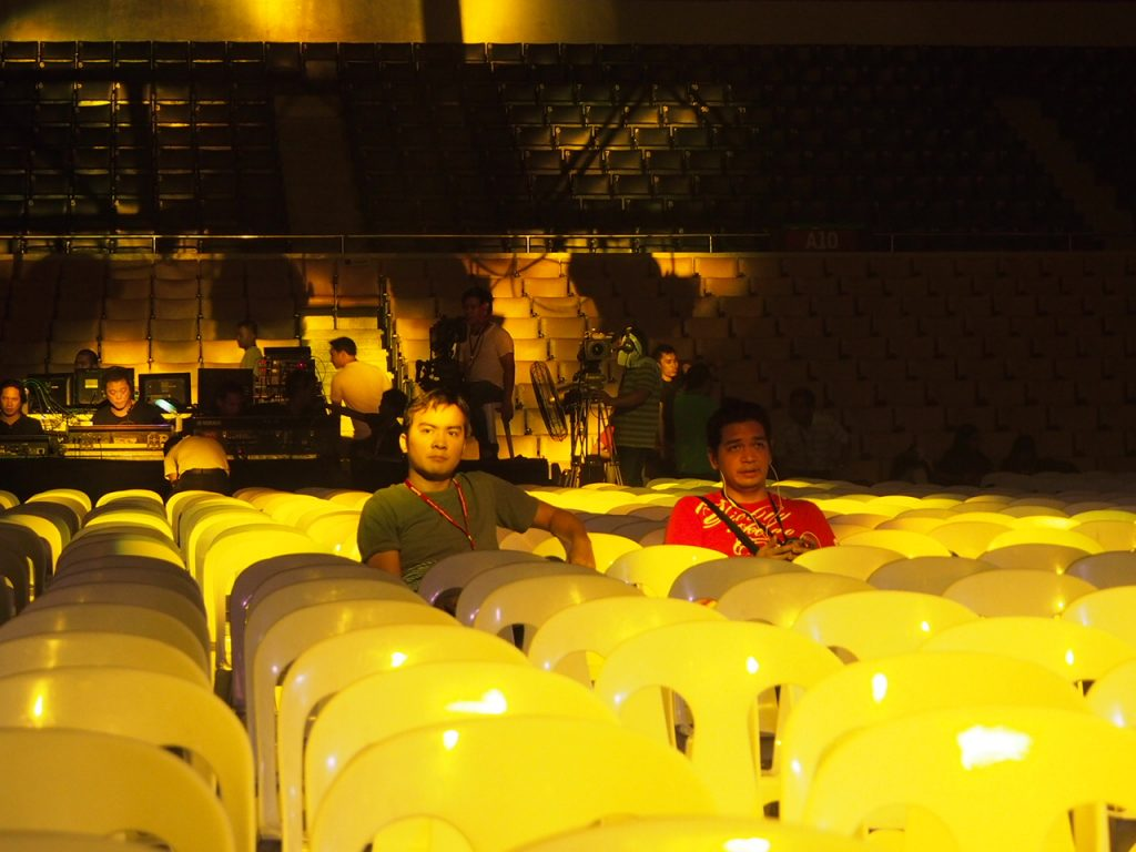 Carlos and me sitting in a mostly empty Cuneta Astrodome, watching the technical dress rehearsal.